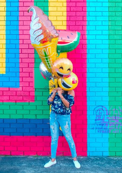 Woman covering face with assorted balloons